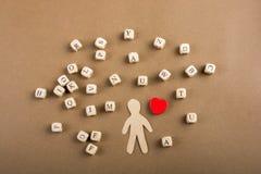 Les cubes en lettre et la figurine et le coeur en bois d'homme forment Image libre de droits