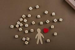 Les cubes en lettre et la figurine et le coeur en bois d'homme forment Image stock