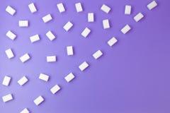 Les cubes en sucre blanc ont arrangé dans les lignes diagonales sur le fond pourpre Photo stock