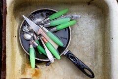 Les cuillères, les fourchettes et les couteaux sales sont dans la vieille casserole dans l'évier af Image stock