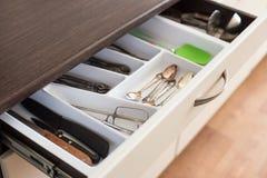 Les cuillères, les fourchettes et les couteaux dans les couverts enferment dans une boîte le tiroir Photographie stock