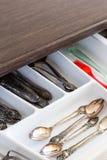 Les cuillères, les fourchettes et les couteaux dans les couverts enferment dans une boîte le tiroir Photos stock
