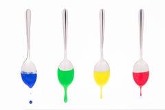 Les cuillères suspendues se sont baignées en peinture colorée avec la peinture liquide Photographie stock libre de droits