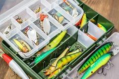 Les cuillers, leurre, les mouches, attirail dans la boîte pour pêcher ou pêcher un poisson prédateur sur le fond en bois de plate Photographie stock libre de droits