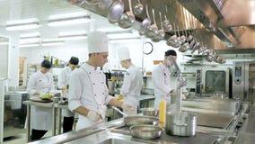 Les cuisiniers préparent des repas sur le fourneau dans la cuisine du restaurant ou de l'hôtel banque de vidéos