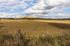 Les cumulus épais de l'été se trouvent au-dessus d'un champ sec large en Toscane Italie Image libre de droits