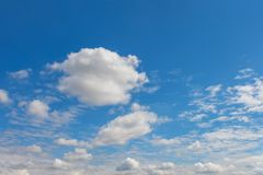 Les cumulus blancs luxuriants nagent à travers le ciel bleu images stock