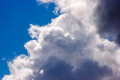 Les cumulus blancs luxuriants nagent à travers le ciel bleu photographie stock libre de droits