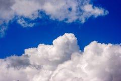 Les cumulus blancs luxuriants nagent à travers le ciel bleu photo stock