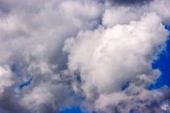 Les cumulus blancs luxuriants nagent à travers le ciel bleu image stock