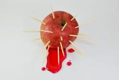Les cure-dents poignardent dans l'écoulement liquide rouge de pomme et de rouge Photos stock