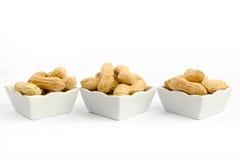 Trois cuvettes blanches remplies d'arachides sur un fond blanc Images stock