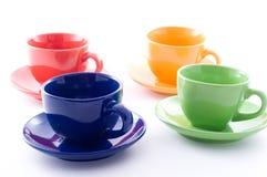 les cuvettes colorées de café ont isolé le blanc image stock