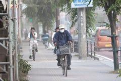 Les cyclistes brave la cendre après éruption volcanique Photos libres de droits