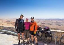 Les cyclistes heureux d'amis détendent dans la belle vue du désert de l'Israël Photo libre de droits
