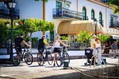 Les cyclistes maintiennent les vélos et la marche dans Puerto De Mogan Photographie stock libre de droits