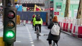 Les cyclistes montent dans une ruelle occupée de cycle à Londres avec des feux de signalisation de cycle par le chantier de const banque de vidéos