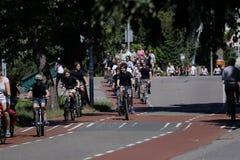 Les cyclistes montent sur la ruelle de bycicle dans Aalsmeer, Pays-Bas images libres de droits