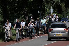 Les cyclistes montent sur la ruelle de bycicle dans Aalsmeer, Pays-Bas image stock
