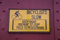 Les cyclistes ralentissent le signe Images stock