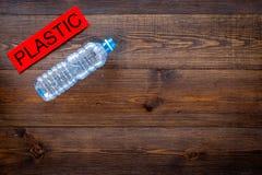 Les déchets appropriés à réutilisent Bouteille en plastique près de plastique de mot sur l'espace en bois foncé de copie de vue s images stock