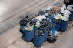 Les déchets contre de pleines poubelles avec des déchets mettent en sac le débordement dessus images libres de droits