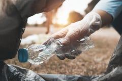 les déchets de bouteille de participation de main mettant dedans pour noircir le sac pour réutilisent image stock