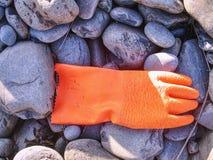 Les déchets en plastique et caoutchouteux ont lavé sur une plage pierreuse images stock