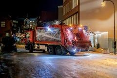 Les déchets rassemblant le camion se déplacent le long de la rue de ville Heure foncée image stock
