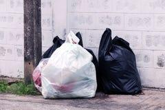Les déchets sont des sorts de pile vident, les déchets de noir de beaucoup de déchets de sachets en plastique au village de la co photo libre de droits