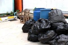 Les déchets sont des sorts de pile vident, les déchets de noir de beaucoup de déchets de sachets en plastique au village de la co image libre de droits