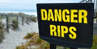 Les déchirures de danger des courants forts signent signalé sur le beac Photographie stock