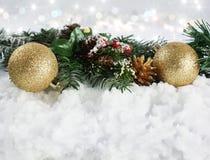 Les décorations de Noël dans la neige avec le bokeh allume le fond Photographie stock libre de droits
