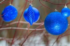 Les décorations extérieures de Noël avec la babiole brillante d'outre-mer ornemente accrocher sur des branches de rouge d'arbre image libre de droits