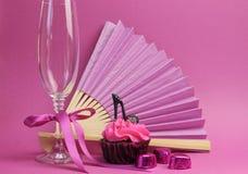 Les décorations roses de partie avec la fan, le verre de champagne et le talon haut chaussent le petit gâteau Images stock