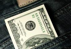 Les dénominations dans la dénomination de cent dollars dans des jeans empochent le plan rapproché Photographie stock libre de droits