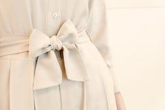 Les détails du lien de ceinture d'arc dans la femme beige habillent le style d'équipement Mode dernier cri Images stock