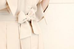 Les détails du lien de ceinture d'arc dans la femme beige habillent le style d'équipement Mode dernier cri Photographie stock