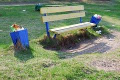 Les d?chets sont ? c?t? de la poubelle pr?s du banc en parc Plein coffre d'ordures D?chets de plastique photographie stock libre de droits