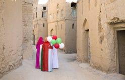 Les dames couvertes de drapeaux omanais, se tenant monte en ballon la marche les rues de la vieille ville Al Hamra photo stock