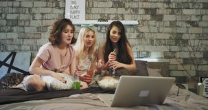 Les dames d'adolescent d'amis de bête ont une partie de sleepover, sur le lit qu'elles observent une comédie sur le carnet, souri banque de vidéos