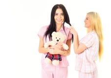 Les dames sur les visages de sourire avec l'ours de jouet de peluche semblent mignonnes Concept de fille de loisirs Filles dans d Photos libres de droits