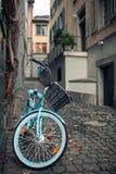Les dames vont à vélo avec le panier garé sur la rue sur le vieil Européen Photographie stock libre de droits