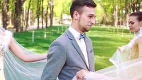 Les danseurs f?minins dans des costumes nuptiales marchent autour de l'homme dans le costume de mari? en parc ensoleill? banque de vidéos