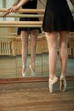 Les danseurs minces de jambes s'approchent du barre photo stock