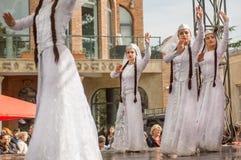 Les danseuses de jeunes filles dans le blanc géorgien traditionnel habille la danse sur l'étape Image libre de droits