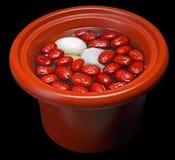 Les dates rouges cuisent l'oeuf de ragoût en isolation sur le noir Photos libres de droits
