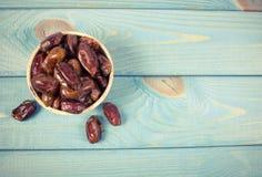 Les dattes sèches portent des fruits dans la cuvette, sur le fond en bois Photographie stock libre de droits