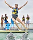 Les dauphins jettent la fille en l'air hors de l'eau Photos libres de droits