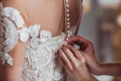 Les demoiselles d'honneur aidant à porter la robe de mariage pour la jeune mariée Photographie stock libre de droits